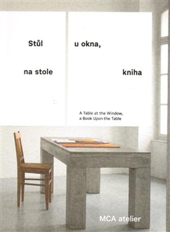 Stůl u okna, na stole kniha